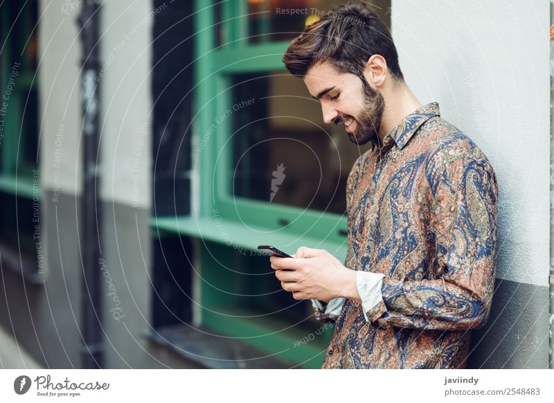 Young smiling man looking at his smartphone in the street Lifestyle Style Beautiful Hair and hairstyles Telephone PDA Human being Masculine Young man