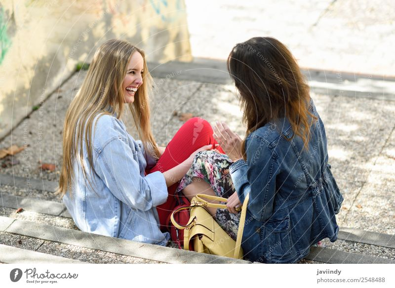 Two young women talking and laughing on urban steps Woman Human being Youth (Young adults) Young woman Beautiful White Joy 18 - 30 years Street Lifestyle Adults