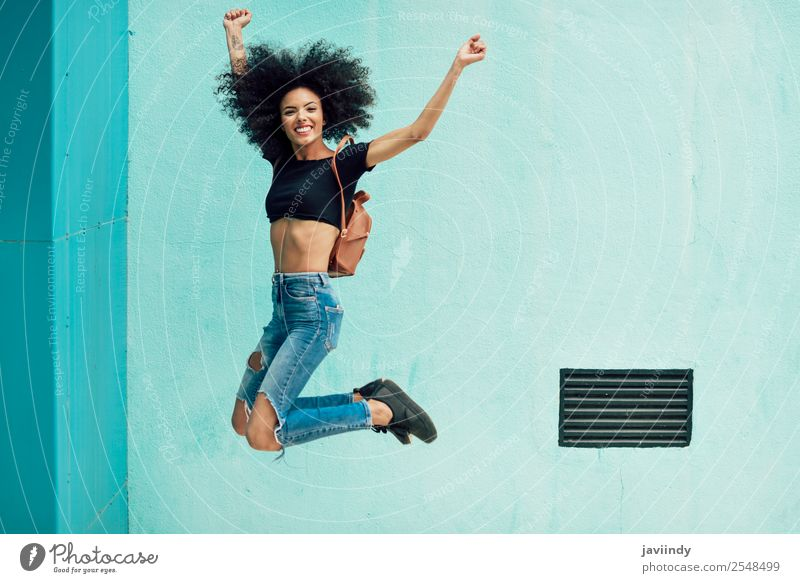 Young mixed woman with afro hair jumping outdoors Woman Human being Youth (Young adults) Young woman Joy 18 - 30 years Black Face Street Lifestyle Adults