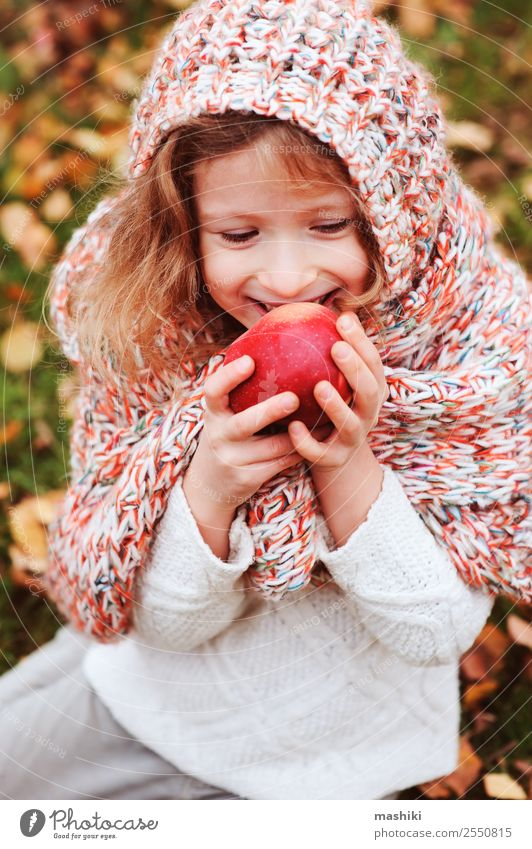 kid girl eating fresh apple in autumn garden Fruit Apple Lifestyle Joy Playing Garden Child Infancy Nature Autumn Warmth Leaf Forest Scarf Smiling Happiness