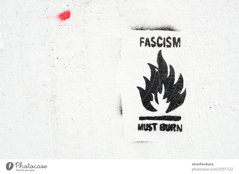 Graffiti against fascism with stylized flame, black writing on white wall House (Residential Structure) Wall (barrier) Wall (building) Stone Concrete Sign