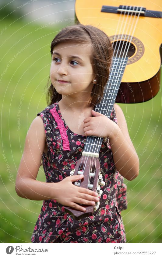 Girl with a guitar on the green grass Music Child School Human being Boy (child) Guitar Musical notes Flower Grass Green Pink girl student spanish handsome