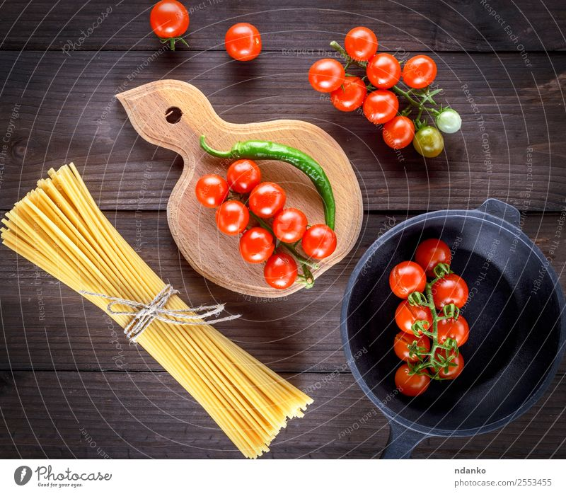 raw spaghetti and red cherry tomatoes Vegetable Dough Baked goods Dinner Pan Table Wood Fresh Yellow Red White pasta food background Raw Spaghetti Tomato