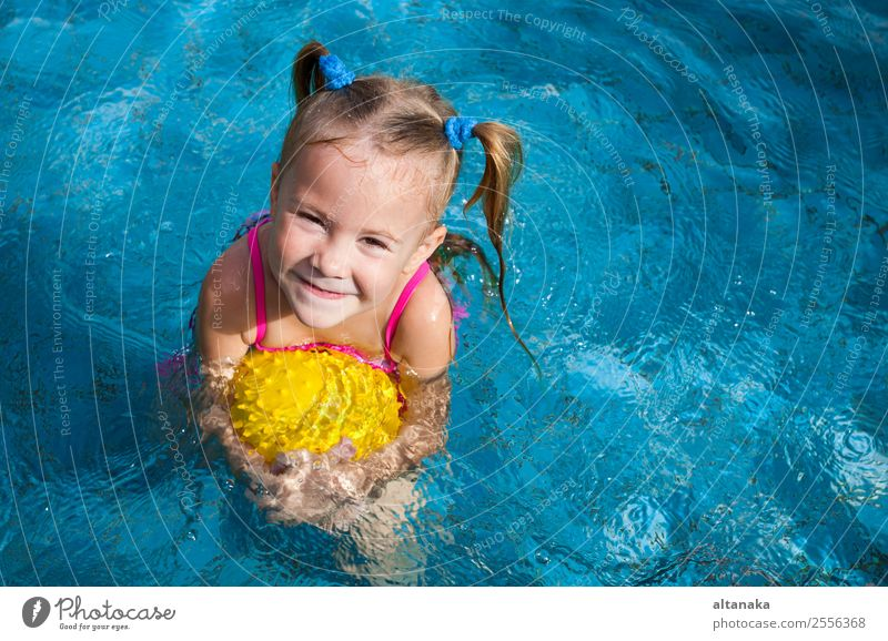 happy little girl playing in the pool with ball Lifestyle Joy Happy Face Relaxation Swimming pool Leisure and hobbies Playing Vacation & Travel Summer Sun