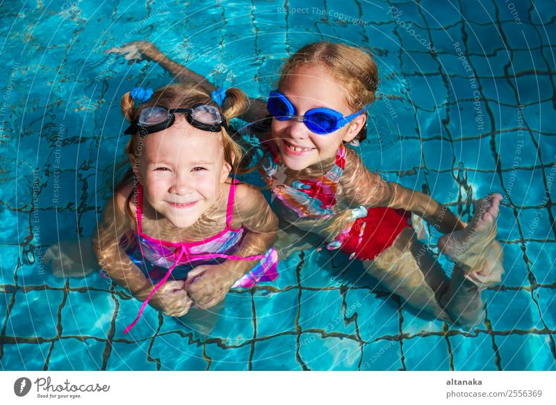 two little girls playing in the pool Lifestyle Joy Happy Face Relaxation Swimming pool Leisure and hobbies Playing Vacation & Travel Summer Sun Sports Child