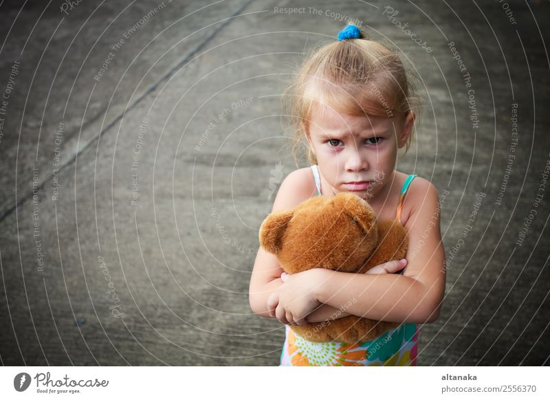 ad little girl holding toy with her hands Face Child Human being Woman Adults Infancy Street Blonde Toys Think Sadness Cute Emotions Concern Grief Fatigue Pain