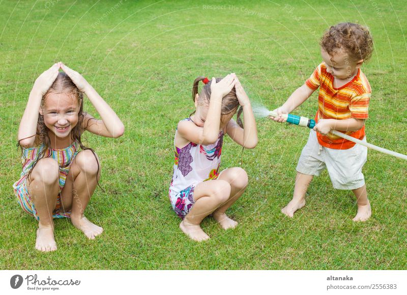 Happy children pours a water Child Human being Nature Man Summer Green House (Residential Structure) Joy Adults Movement Family & Relations Grass Boy (child)