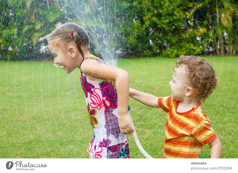 little boy is pouring a water from a hose at her sister Joy Happy Leisure and hobbies Playing Summer House (Residential Structure) Garden Child Human being