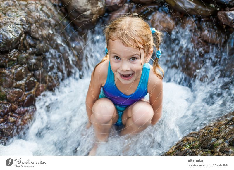 happy girl sitting near the waterfall Lifestyle Joy Happy Face Relaxation Swimming pool Leisure and hobbies Playing Vacation & Travel Summer Child