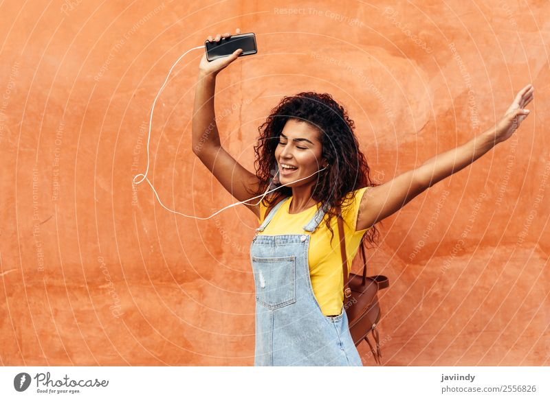 Happy Arab girl listening to music and dancing outdoors Woman Human being Youth (Young adults) Young woman Beautiful Joy 18 - 30 years Black Street Lifestyle