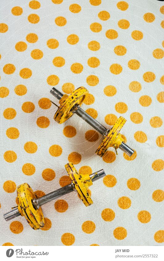 Yellow antique weights on a polka dot towel Lifestyle Sports Fitness Sports Training Metal Steel Rust Diet Old Athletic Free Strong Power Flexible Resolve