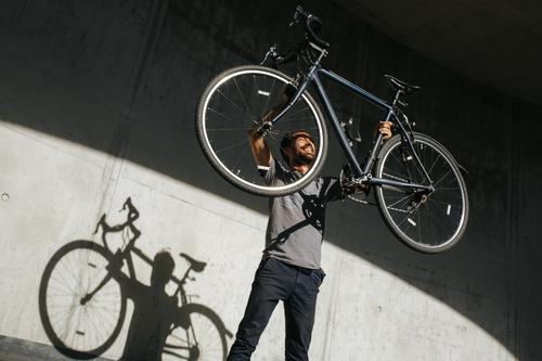 Man lifts his bike up in the air Lifestyle Joy Leisure and hobbies Vacation & Travel Trip Freedom Summer Fitness Sports Training Cycling Bicycle Masculine