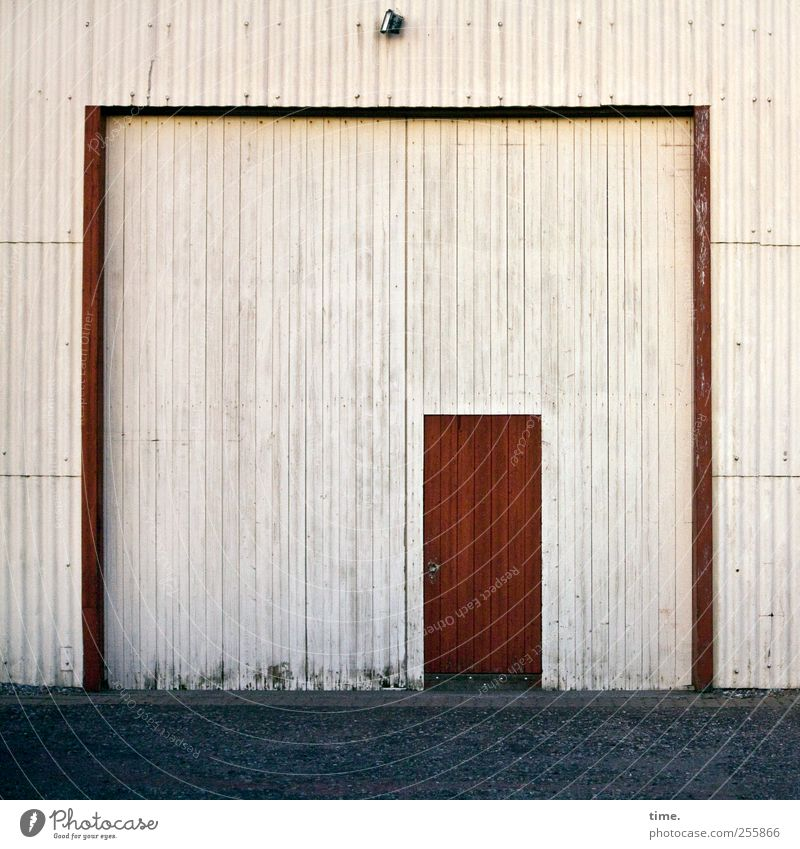Get that door up. Nobody's illegal. Contentment Lamp Foliage plant Architecture Barn Warehouse Storage shed Door Street Red Symmetry Corrugated sheet iron Dusk