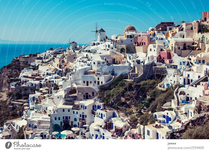 View over the white houses in Oia, Santorini, by day, with old windmills coast Summer Windmill Vacation & Travel Exterior shot the Aegean Colour photo