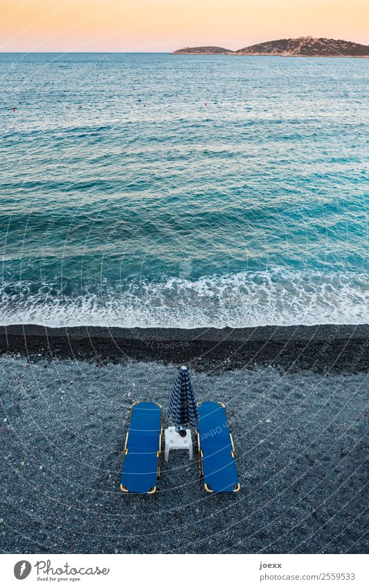 Two blue beach chairs with parasol and small tables on the dark beach with turquoise sea in front of sunset from above Lie Blue Sunshade Beach Black
