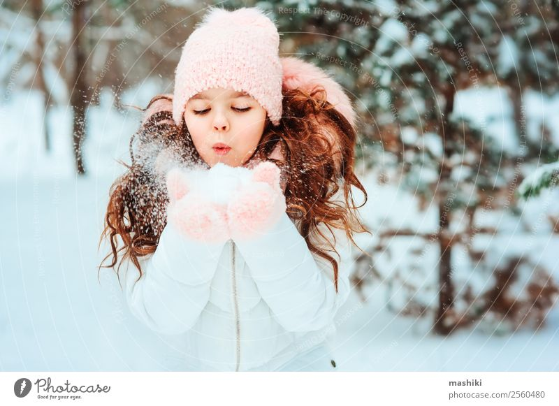 Winter portrait of happy kid girl playing outdoor Joy Vacation & Travel Adventure Freedom Snow Child Infancy Nature Snowfall Tree Park Forest Fashion Clothing