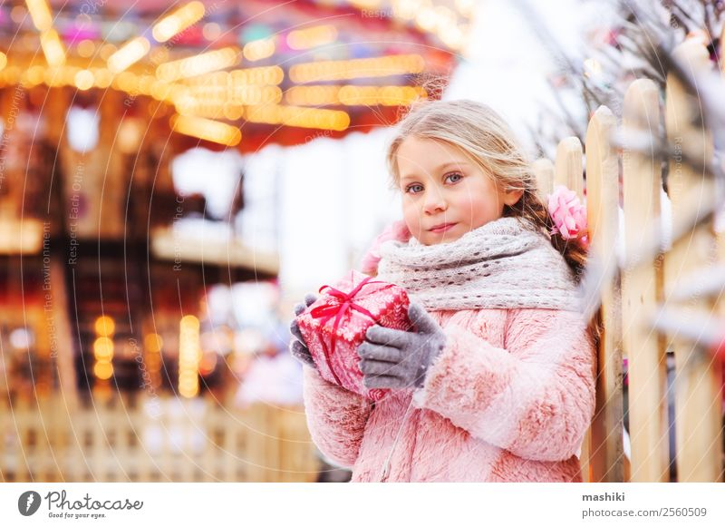 happy child girl holding christmas gift outdoor on the walk Shopping Winter Snow Decoration New Year's Eve Child Infancy Fashion Fur coat Scarf Hat Souvenir
