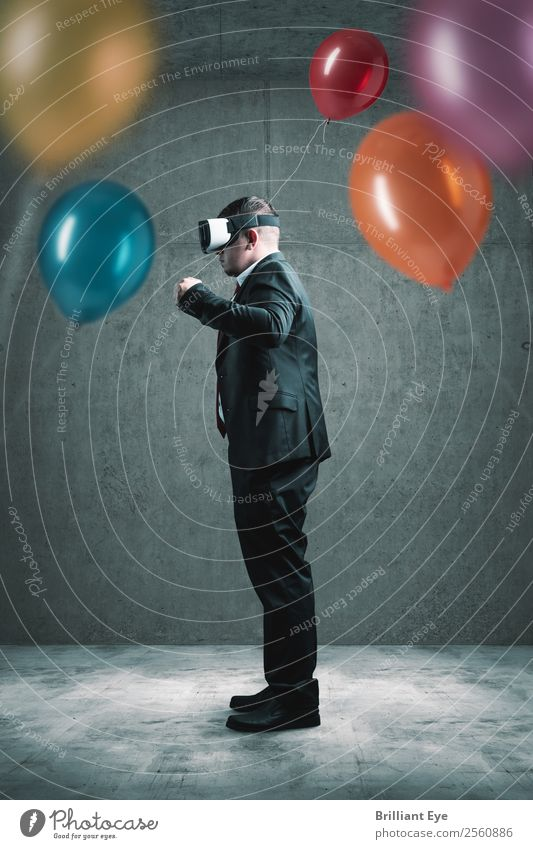 businessman standing with VR headset on concrete floor and holding red balloon in hand in front of lot other colorful balloons Lifestyle Joy Leisure and hobbies