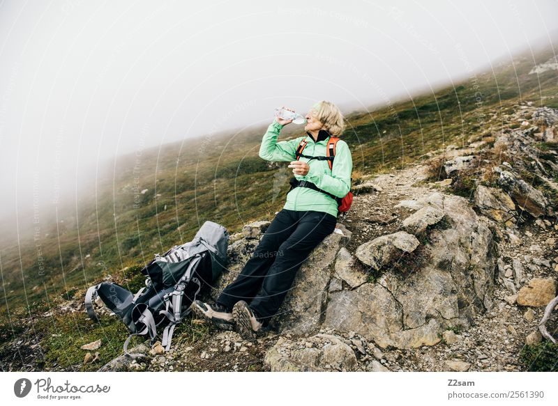 Pensioner drinks on the mountain top Mountain Hiking Female senior Woman 1 Human being 60 years and older Senior citizen Nature Landscape Autumn Bad weather Fog