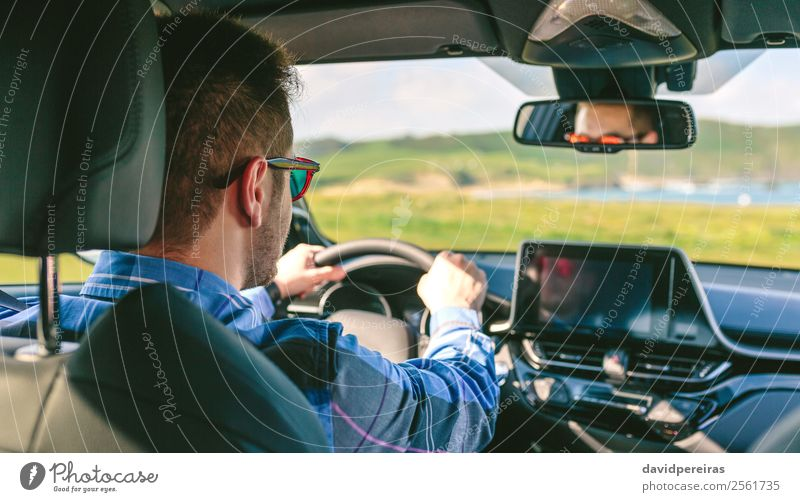 Young man holding steering driving Lifestyle Vacation & Travel Trip Adventure Screen Technology Human being Man Adults Arm Hand Grass Meadow Coast Transport