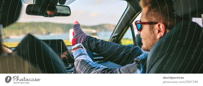 Young man resting feet up sitting on the car Lifestyle Joy Happy Relaxation Leisure and hobbies Vacation & Travel Trip Adventure Human being Man Adults Coast