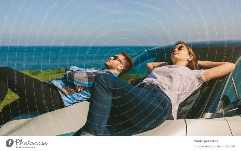 Young couple lying on the windshield Woman Human being Nature Vacation & Travel Man Landscape Ocean Relaxation Calm Lifestyle Adults Coast Style Couple Freedom