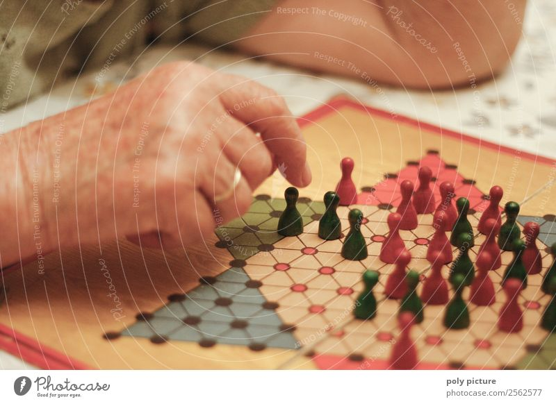 Pensioner plays Halma Leisure and hobbies Playing Woman Adults Female senior Male senior Man Grandparents Senior citizen Grandfather Grandmother Life Hand
