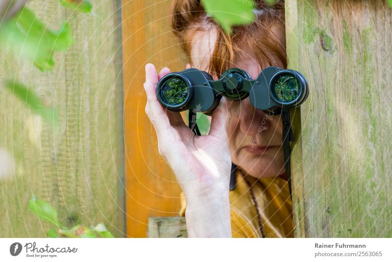a woman watching through binoculars Human being Feminine Woman Adults Head Hand 1 Nature Garden Red-haired Binoculars Observe Curiosity Interest Revenge