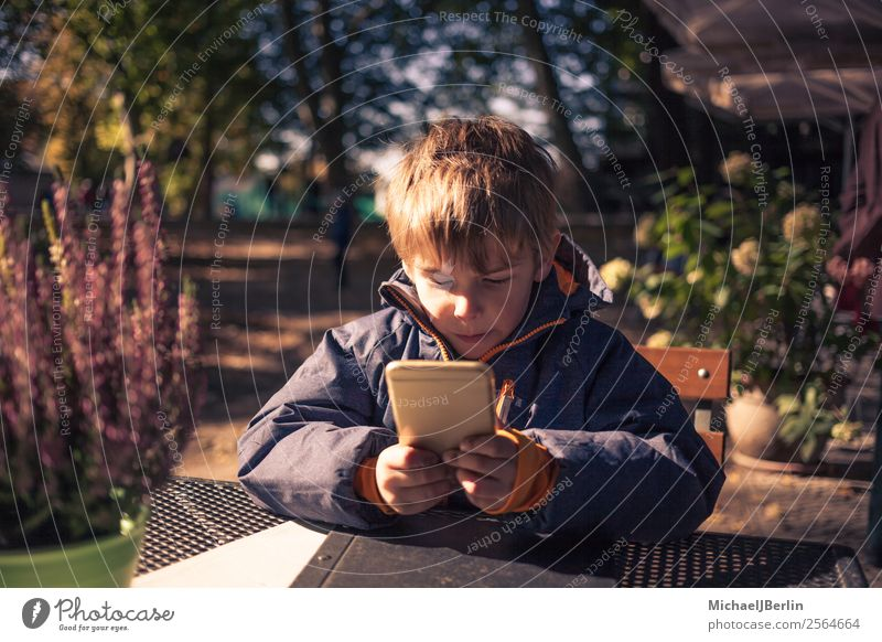 Child with smartphone sits outside in autumn Human being Masculine Boy (child) Infancy 1 3 - 8 years Autumn Playing Jacket Autumnal Cold Fresh Exterior shot PDA