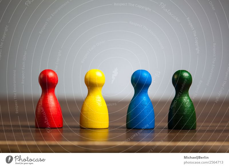 Four game figures on a table in various colours Playing Business Blue Multicoloured Yellow Green Red Symbols and metaphors Versatile Difference different