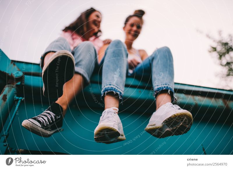 two cheeky women sitting on big container Lifestyle Joy Happy To talk Human being Woman Adults Friendship Jeans Sneakers Laughter Brash Funny Perspective young
