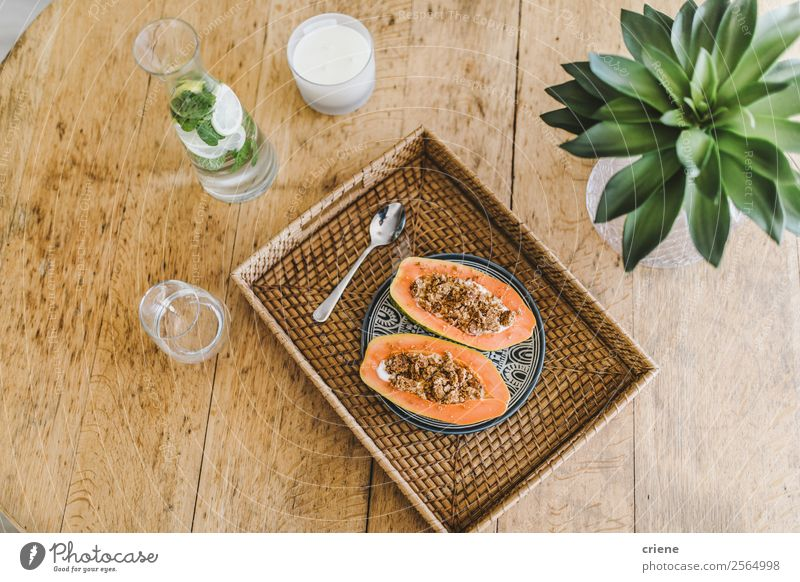 closup of preparing papaya with cereals in kitchen Yoghurt Fruit Dessert Vegetarian diet Diet Exotic Summer Table Nature Plant Leaf Wood Fresh Delicious Natural