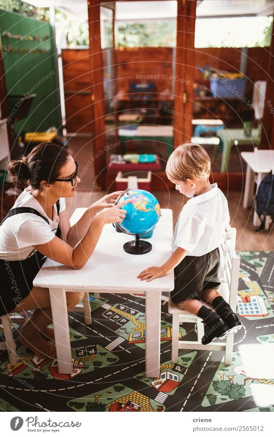 young boy studying with teacher in class room Happy Desk Child School Classroom Teacher Human being Boy (child) Woman Adults Man Book Globe Sit Small