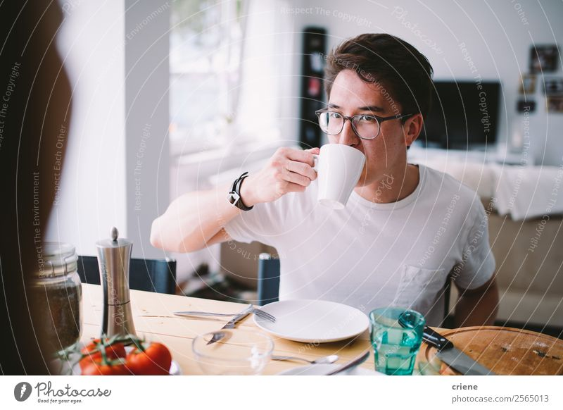 young asian man drinking coffee while having breakfast Vegetable Eating Breakfast Coffee Joy Beautiful Chair Table Kitchen To talk Human being Woman Adults Man