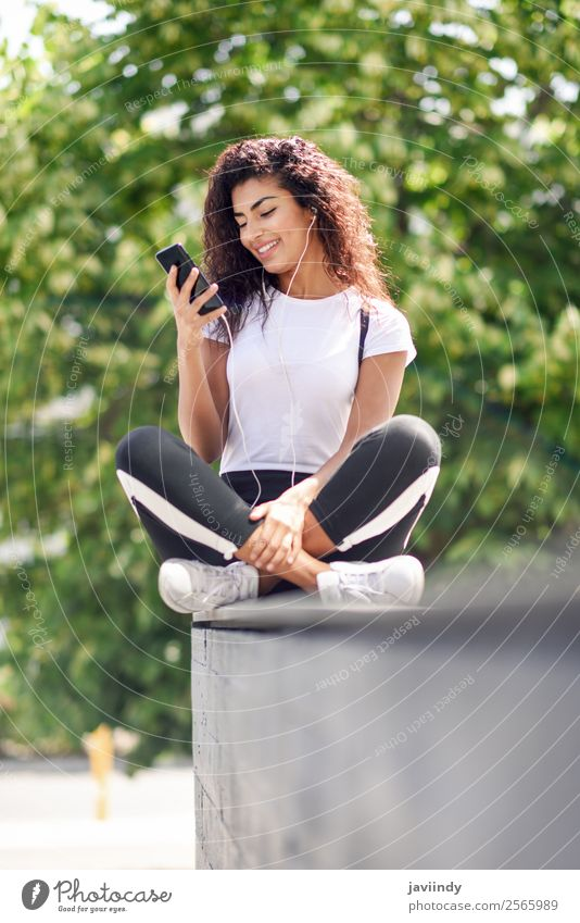 Beautiful African woman listening to music with earphones Lifestyle Style Happy Hair and hairstyles Music Sports Telephone PDA Technology Human being Feminine