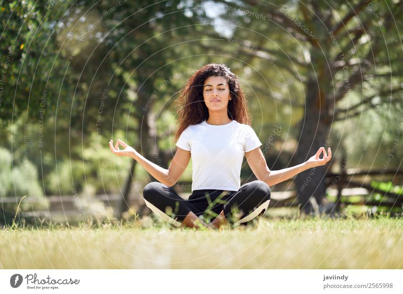 Young woman doing yoga on the grass of urban park. Lifestyle Happy Hair and hairstyles Relaxation Calm Meditation Summer Sports Yoga Human being Feminine