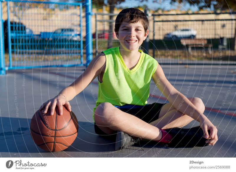 Young basketball player sitting on the court Lifestyle Joy Relaxation Leisure and hobbies Playing Sports Boy (child) Man Adults Youth (Young adults) Street Sit