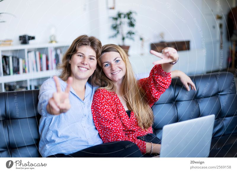 happy teenage girls sitting on a sofa Lifestyle Shopping Joy Happy Beautiful Contentment Leisure and hobbies Sofa Success To talk Computer Notebook Technology