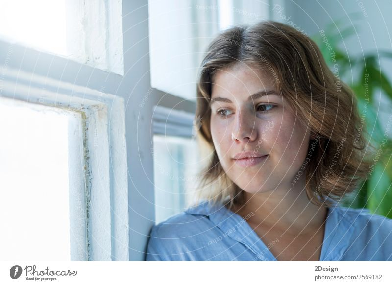 Woman leaning on a window, looking out of window Human being Youth (Young adults) Young woman Beautiful White Relaxation Loneliness 18 - 30 years Face Lifestyle