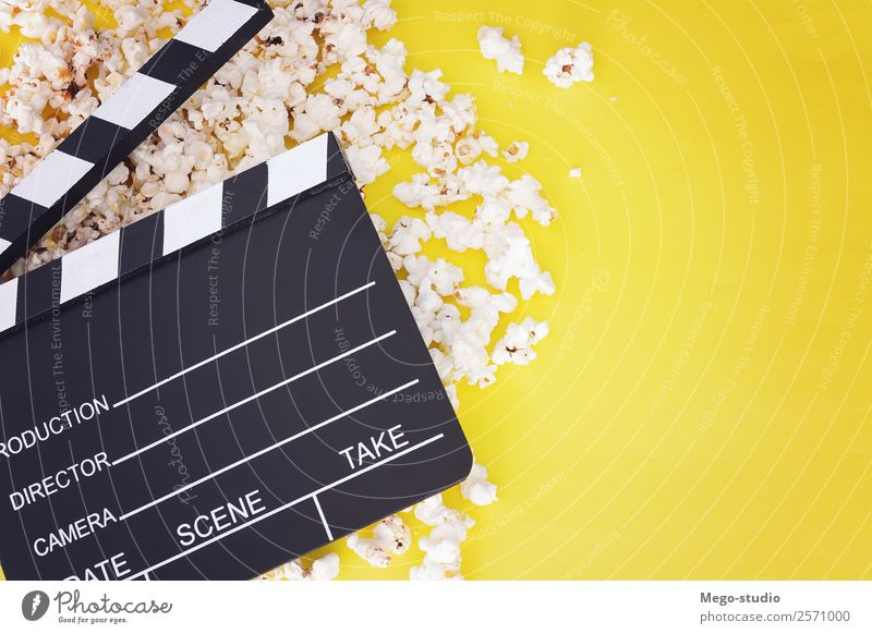 popcorn and clapboard on yellow background. Cinema concept Fast food Bowl Joy Leisure and hobbies Entertainment Industry Theatre Media Television Wood Observe