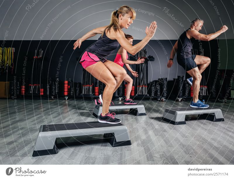 Woman trainer doing aerobic class with steppers in gym Lifestyle Happy Beautiful Sports Human being Adults Man Friendship Group Fitness Jump Authentic Eroticism