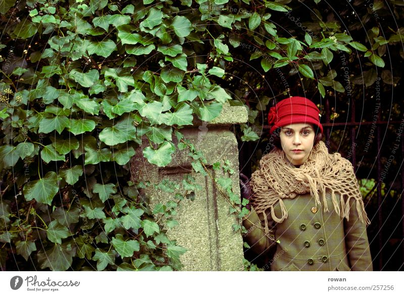earnestness Human being Feminine Young woman Youth (Young adults) 1 Bushes Leaf Wall (barrier) Wall (building) Hat Red Green Ivy Overgrown Gate Garden