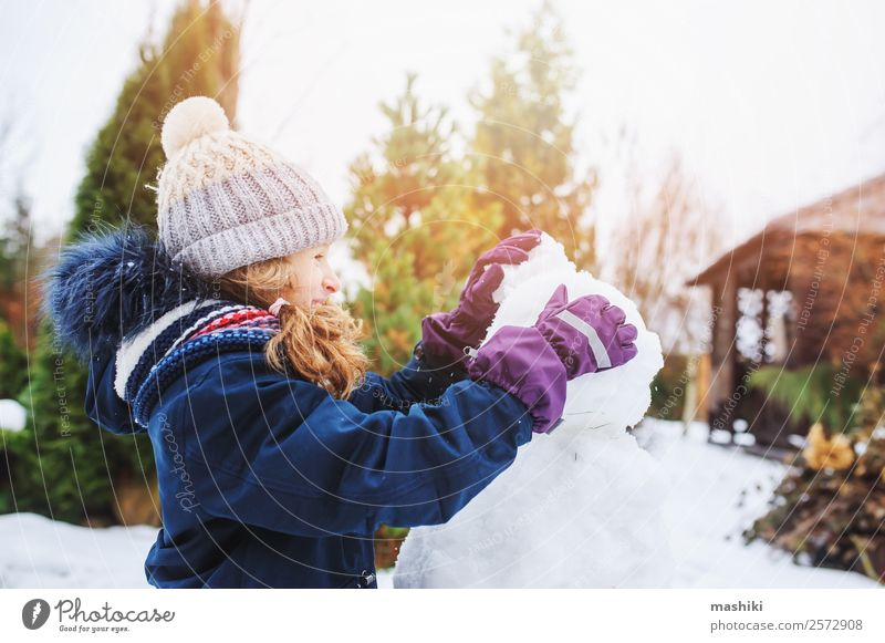 happy kid girl making snow man on Christmas vacations Joy Leisure and hobbies Playing Vacation & Travel Winter Snow Garden Child Nature Weather Park Clothing