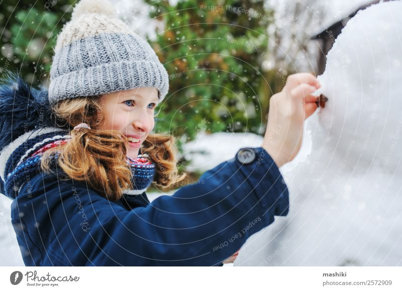happy kid girl making snow man on Christmas Child Nature Vacation & Travel Joy Winter Snow Garden Playing Leisure and hobbies Park Weather Action Clothing Make