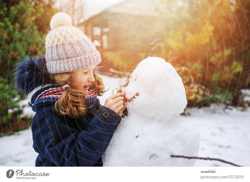 happy kid girl making snow man on Christmas vacations Joy Leisure and hobbies Playing Vacation & Travel Winter Snow Winter vacation Garden Child Nature Weather
