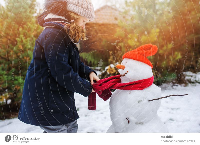 happy kid girl making snow man Child Nature Vacation & Travel Joy Winter Snow Garden Playing Leisure and hobbies Park Weather Action Clothing Make Delightful