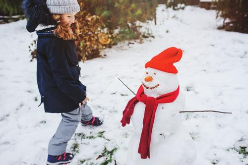 happy kid girl making snow man Joy Leisure and hobbies Playing Vacation & Travel Winter Snow Garden Child Nature Weather Park Clothing Make Snowman walk Action
