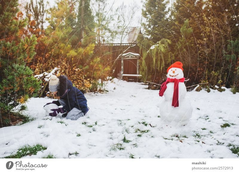 happy kid girl making snow man on Christmas Joy Leisure and hobbies Playing Vacation & Travel Winter Snow Garden Child Nature Weather Park Clothing Make Snowman