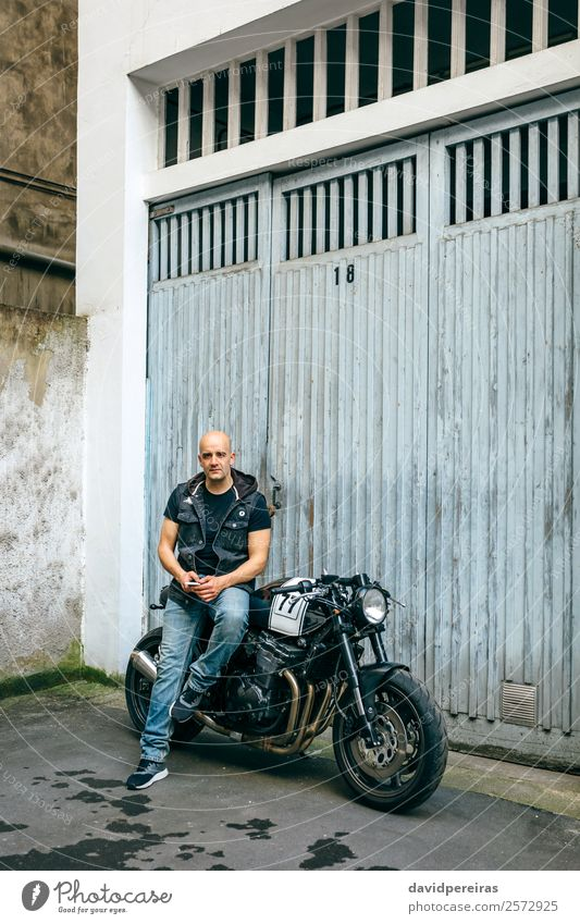 Biker posing with a motorcycle Lifestyle Style Trip Engines Human being Man Adults Street Vehicle Motorcycle Bald or shaved head Sit Authentic Retro Black Pride