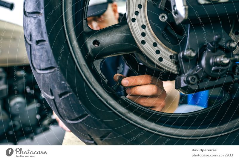 Mechanic placing motorcycle wheel valve Lifestyle Style Work and employment Human being Man Adults Hand Vehicle Motorcycle Authentic Retro mechanic fixing up